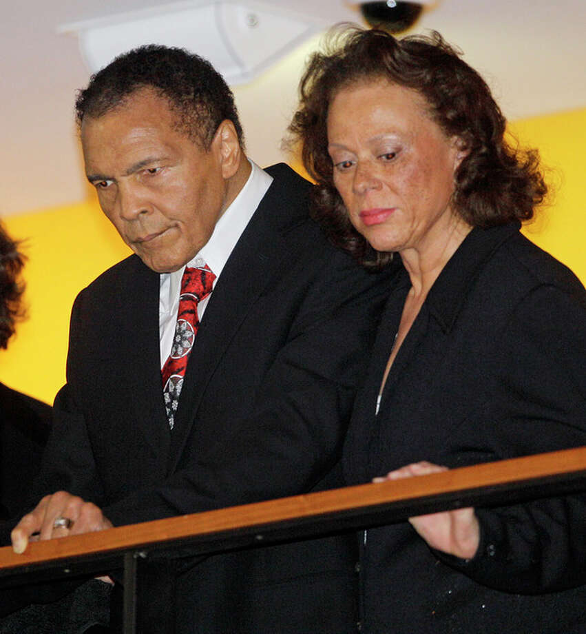 Boxing great Muhammad Ali, with his wife, Lonnie, right, looks down from a balcony at friends attending a celebration for his 70th birthday at the Muhammad Ali Center on Saturday, Jan. 14, 2012, in Louisville, Ky. Ali turns 70 Tuesday. (AP Photo/Mark Humphrey) / AP