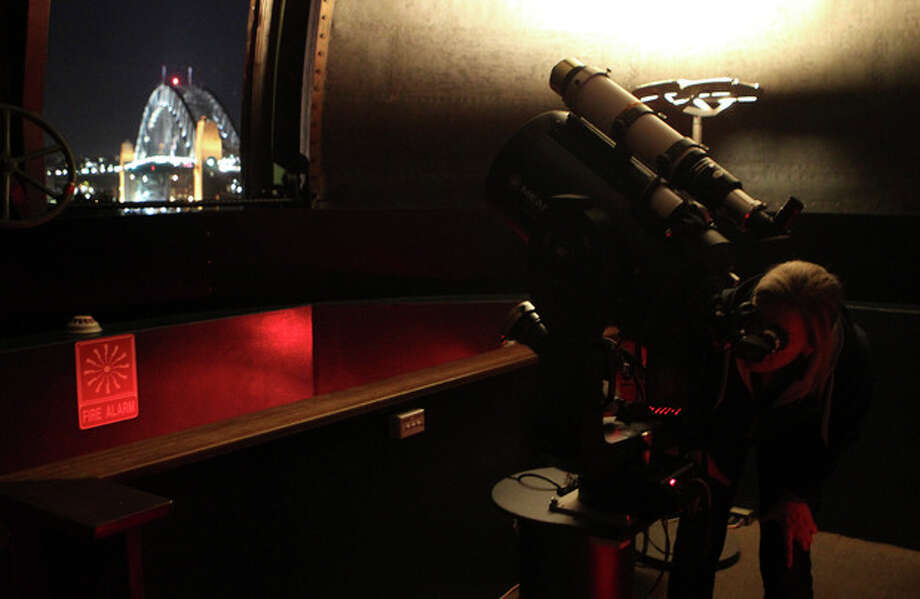 A woman uses a telescope at the Sydney Observatory to watch the moon over the Harbour Bridge during a total lunar eclipse in Sydney, Australia, Sunday, Dec. 11, 2011. (AP Photo/Rob Griffith) / AP