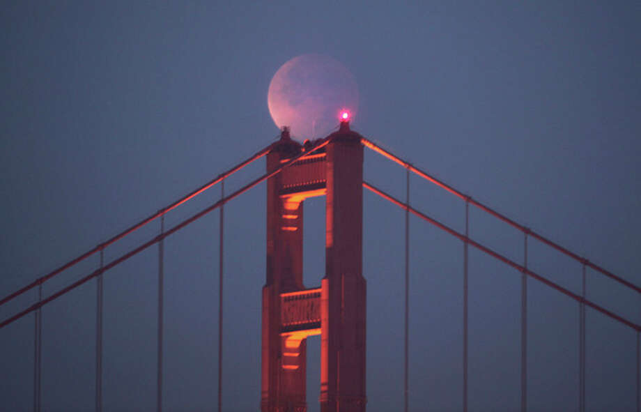 The moon is seen in the sky over the Golden Gate Bridge during an eclipse on Saturday, Dec. 10, 2011, in San Francisco. The next full eclipse of the moon will not happen until April 14, 2014. (AP Photo/San Francisco Chronicle, Frederic Larson) NORTHERN CALIFORNIA MANDATORY CREDIT PHOTOG & CHRONICLE; MAGS OUT; NO SALES; / Frederic Larson©