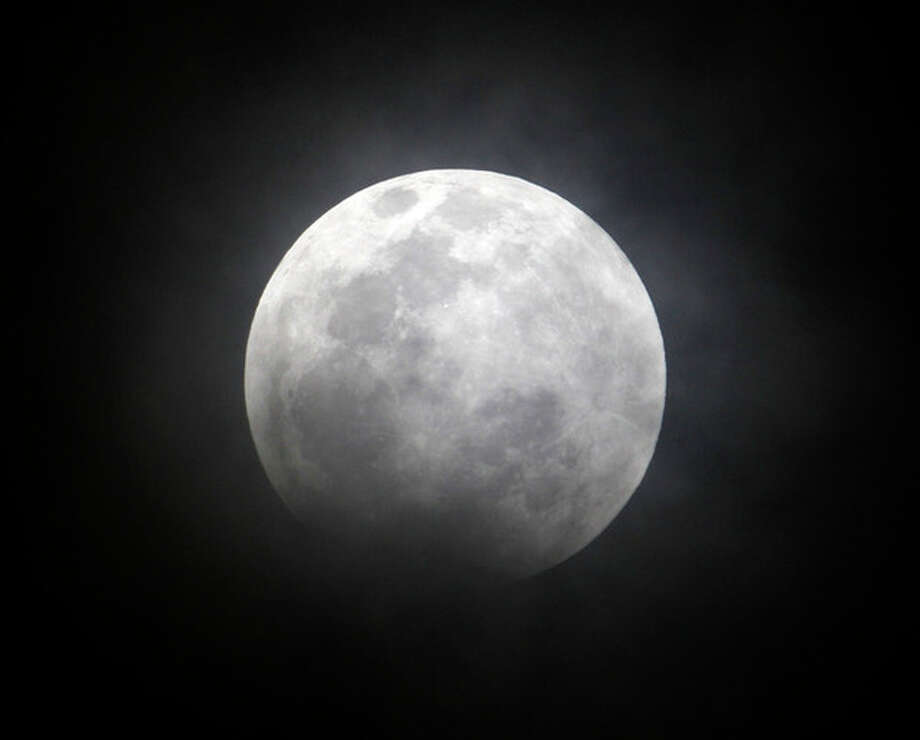 The moon seen from Manila, Philippines, during a total lunar eclipse Saturday Dec. 10, 2011, as the Earth casts a shadow across the face of the moon. Passing clouds hampered the evening spectacle in some parts of the Philippines. (AP Photo/Bullit Marquez) / AP