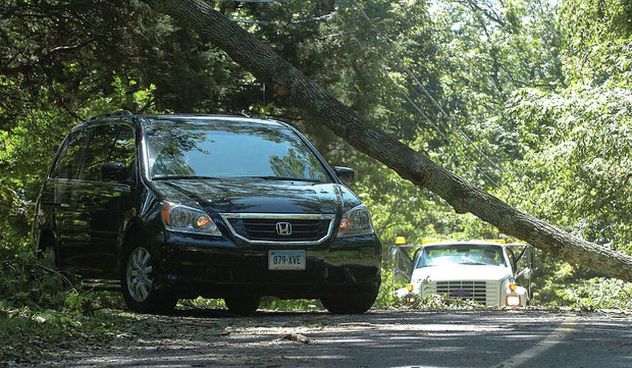 Photo by Alex von Kleydorff. A mini-van negotiates a downed tree in Wilton on Monday. / 2011 The Hour Newspapers