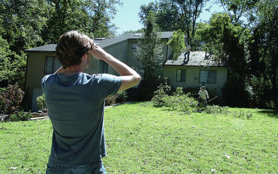 Photo by Alex von Kleydorff. Christopher Williams watches as a fallen tree is cleared from the roof of his Old Kings Highway house in Wilton. / 2011 The Hour Newspapers