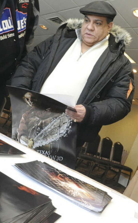 Eddie Rivera picks out a poster to get signed by actor Dan Yeager who plays Leatherface in the Texas Chainsaw films on Sunday at the Doubletree hotel in Norwalk. hour photo/Matthew Vinci