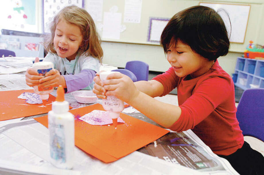 2 year olds in Wilton Parks and Recs' On School Road program, Gabby Coviello and Sofia Lugo, create art projects as part of preschool's daily activities. Hour photo / Erik Trautmann / (C)2011, The Hour Newspapers, all rights reserved