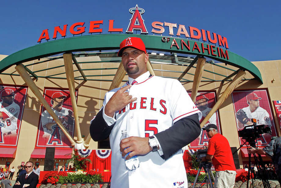 ADVANCE FOR WEEKEND EDITIONS, FEB. 11-12 - FILE - In this Dec. 10, 2011, file photo, Los Angeles Angels Albert Pujols wears his new jersey after a news conference to introduce Pujols and C.J. Wilson (not pictured) as the newest Angels baseball players in Anaheim, Calif. The 14 AL teams have spent $776.8 million on major league contracts for players who became free agents after the World Series and the NL's 16 clubs have committed $597.3 million. (AP Photo/Alex Gallardo, File) / AP2011