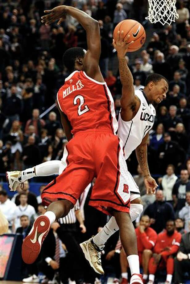 Connecticut's Ryan Boatright, right, is fouled by Rutgers' Dane Miller (2) while driving to the basket during the first half of an NCAA college basketball game in Hartford, Conn., Sunday, Jan. 27, 2013. (AP Photo/Jessica Hill) / FR125654 AP