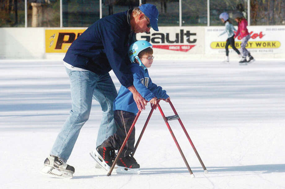 Hour photos / Erik Trautmann Peter Flatow helps his grandson, Brendan Flato, 5, learn how to skate at the Westport Police Athletic League's Outdoor Skating Rink at Longshore in Westport during its opening weekend Saturday. / (C)2011, The Hour Newspapers, all rights reserved