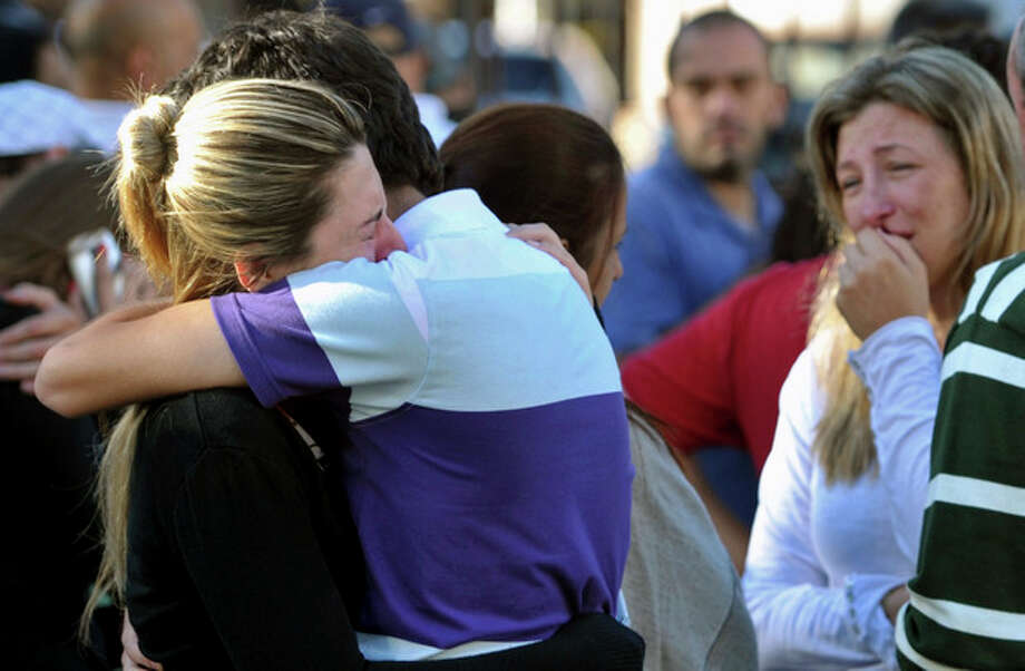 Relatives of victims react near the Kiss nightclub in Santa Maria city, Rio Grande do Sul state, Brazil, Sunday, Jan. 27, 2013. According to police more than 200 died in the devastating nightclub fire in southern Brazil. Officials say the fire broke out at the club while a band was performing. (AP Photo/Ronald Mendes-Agencia RBS) / Agencia RBS