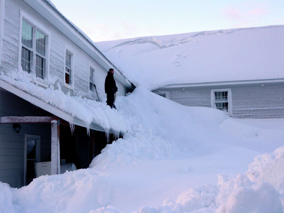 In this Saturday, Jan. 7, 2012 photo provided by the Alaska Division of Homeland Security and Emergency Management, a man stands on a house buried in snow in the fishing town of Cordova, Alaska. Residents have turned to the state to help them dig out of massive snow levels that have collapsed roofs, triggered avalanches and even covered doors, trapping some people in their homes. (AP Photo/Alaska Division of Homeland Security and Emergency Management, Kim Weibl) / Alaska Division of Homeland Security and Emergency Management