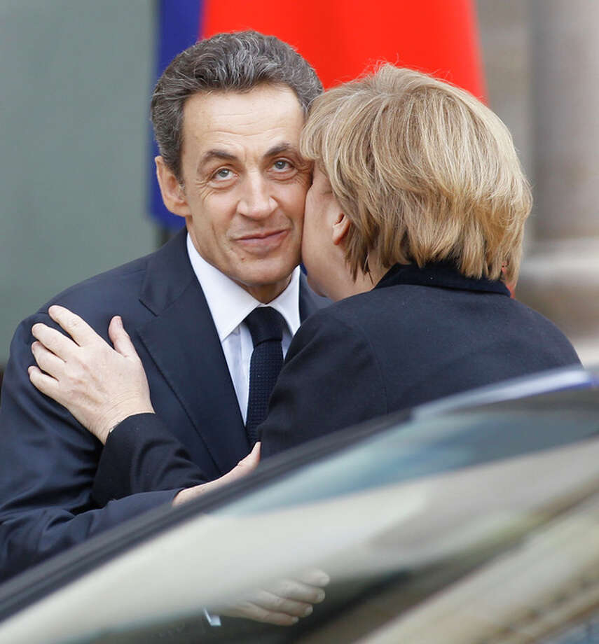 French President Nicolas Sarkozy receives a kiss of greeting from German Chancellor Angela Merkel prior to their meeting at the Elysee Palace in Paris, Monday Dec. 5, 2011. (AP Photo/Remy de la Mauviniere) / AP
