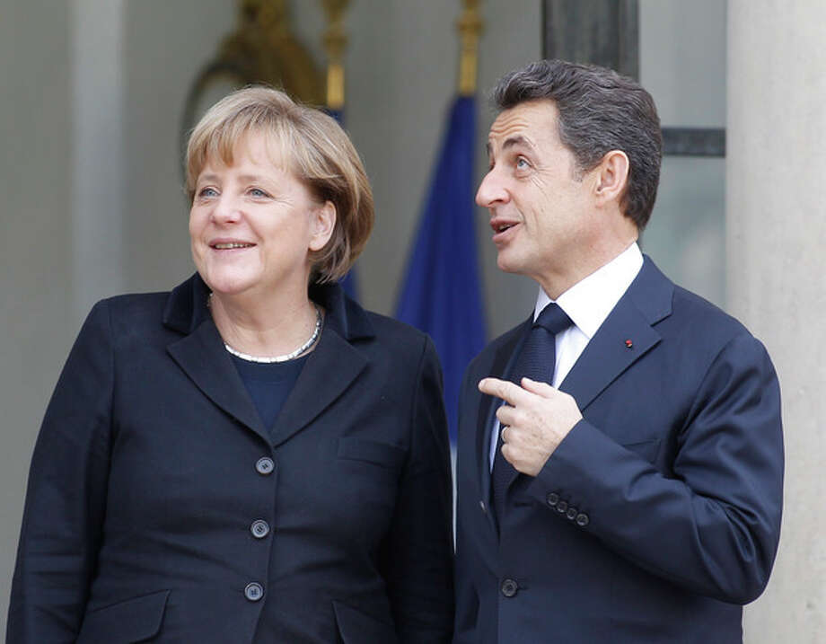 French President Nicolas Sarkozy greets German Chancellor Angela Merkel prior to their meeting at the Elysee Palace in Paris, Monday Dec. 5, 2011.The leaders of Germany and France will try to agree on Monday on a cohesive plan to help save the euro through stricter oversight of government budgets.(AP Photo/Remy de la Mauviniere) / AP