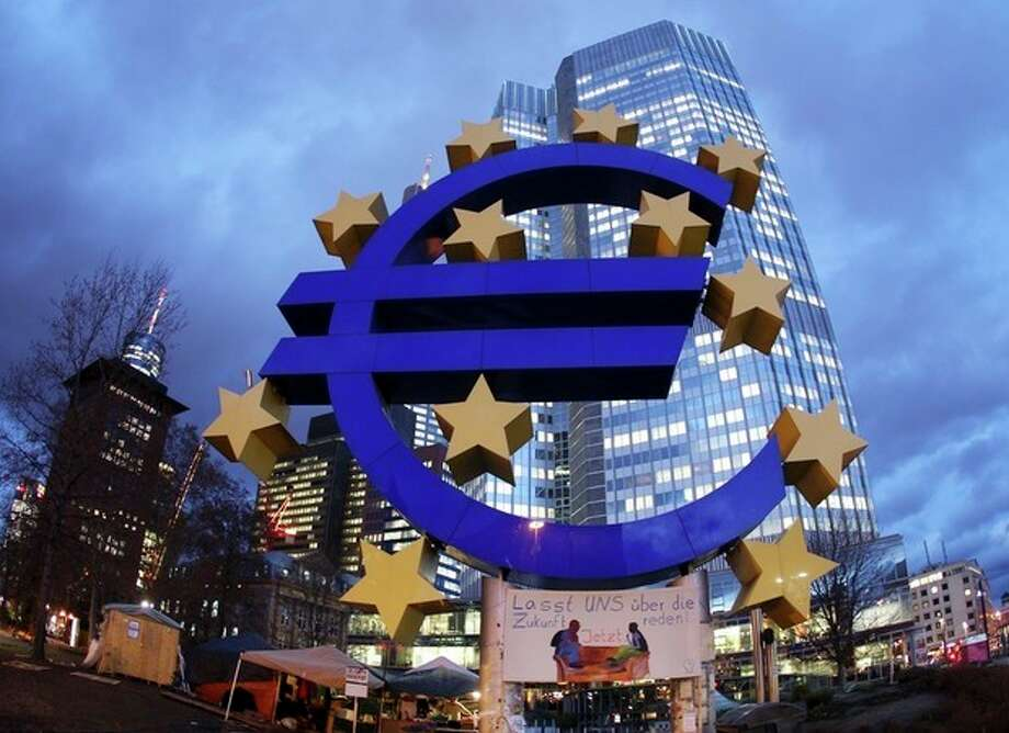 The Euro sculpture stands in front of the European Central Bank, in Frankfurt, Germany, on Friday, Dec.16, 2011. Poster underneath the Euro sign reads: Let's talk about Future. At left tents of the occupy movement still remain. (AP Photo/Michael Probst) / AP