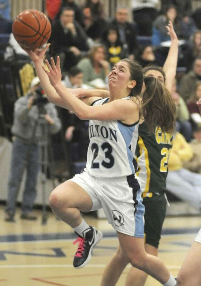 Hour photo/John Nash Wilton's Hayley Tafuro, left, gets hit from behind by Trinity Catholic's Ali Palma during Monday's game at the Zeoli Field House in Wilton. No foul was called on the play. The Warriors turned back the visiting Crusaders, 46-40.