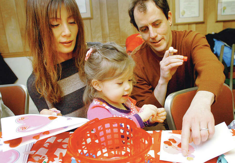 Eve and Tom Bausenwein and their daughter Chloe, 2, create valentines for the 35 to 40 Valentine's 'Craft Baskets' the No Drama Mammas & Pappas of Fairfield County put together at the East Norwalk Library Saturday for the patients at Yale's Pediatric Oncology Unit in New Haven. Hour photo / Erik Trautmann / (C)2011, The Hour Newspapers, all rights reserved