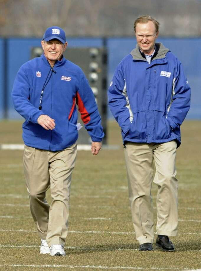 New York Giants coach Tom Coughlin smiles as he walks off the field with owner John Mara, right, after NFL football practice Friday, Jan. 6, 2012, in East Rutherford, N.J. The Giants are slated to host the Atlanta Falcons on Sunday in a wild-card playoff game. (AP Photo/Bill Kostroun)
