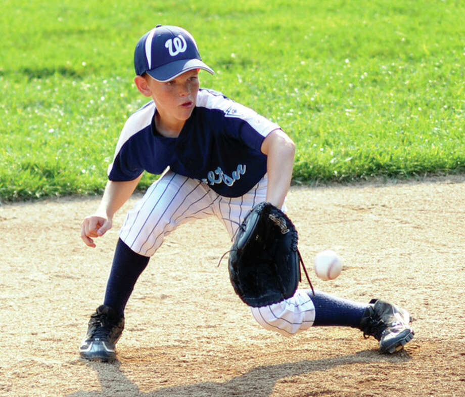 Hour Photo/John Nash WiltonÕs Zach Liston backhands a ground ball for an out during Wednesday's 10-year-old Little League pool play finale. Wilton beat Darien, 4-2.