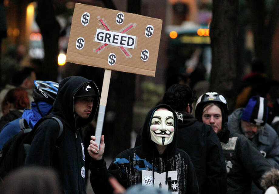 "In this photo taken Wednesday, Nov. 2, 2011, an Occupy Seattle protester wears a Guy Fawkes mask while protesting in downtown Seattle. From New York to San Francisco to London, some of the demonstrators decrying a variety of society's ills are sporting the stylized masks loosely modeled on a 17th-century English terrorist, whether they know it or not. The masks come from ""V for Vendetta,"" a comic-based movie whose violent, anarchist antihero fashions himself as a modern Guy Fawkes, the Catholic insurrectionist executed four centuries ago for trying to blow up Parliament. (AP Photo/Elaine Thompson) / AP"