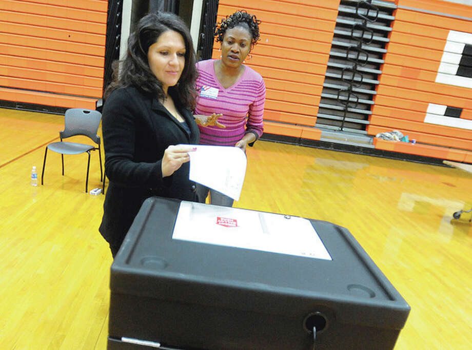 Ballot official Fabiola Placide helps Carol Gonzalez at the polls in Stamford High School Tuesday afternoon. photo/Matthew vinci / (C)2011, The Hour Newspapers, all rights reserved