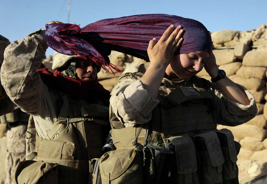 FILE - In this Aug. 10, 2009 file photo, U.S. Marine Sgt. Monica Perez, of San Diego, left, helps Lance Cpl. Mary Shloss of Hammond, Ind. put on her head scarf before heading out on a patrol with Golf Company, 2nd Batallion, 3rd Regiment of the 2nd MEB, 2nd MEF, in the village of Khwaja Jamal in the Helmand Province of Afghanistan. Perez and Shloss are members of the Female Engagement Team whose mission is to engage with local Afghan women. On Thursday, Feb. 9, 2012, Pentagon rules will catch up a bit with reality, recommending to Congress that women be formally allowed to serve in more jobs closer to the front lines. (AP Photo/Julie Jacobson, File) / 2009 AP