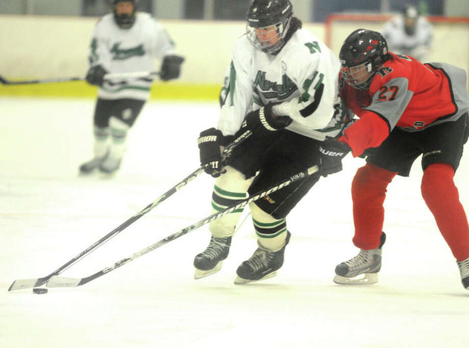 Hour photo/Matthew Vini Mike McRoy, left, of the Norwalk/McMahon co-op hockey team is badgered by Kevin Teskey of the NFA-St. Bernard-Bacon co-op squad during Monday night's non-conference contest at Darien Ice Rink. The Saints made the long ride from the southeastern corner of the state pay off with an 8-0 victory.