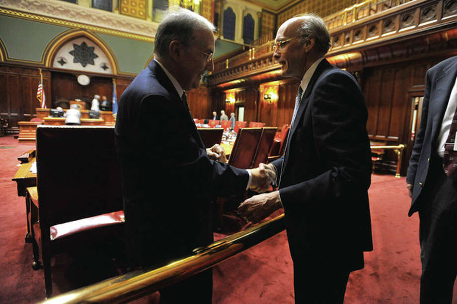 State Senate Majory Leader Martin Looney, D-New Haven, shakes hands with Tim Bannon, Chief of Staff for Gov. Malloy after passage of the UConn lab bill during a special session of the Connecticut General Assembly at the Capitol in Harford, Conn., Wednesday, Oct. 26, 2011. The Senate has passed legislation authorizing nearly $219 million in bonding to help build a $1.1 billion research laboratory at the University of Connecticut in Farmington. The bill passed the Democratic-controlled Senate Wednesday along party lines, 21-14. (AP Photo/Jessica Hill) / AP2011