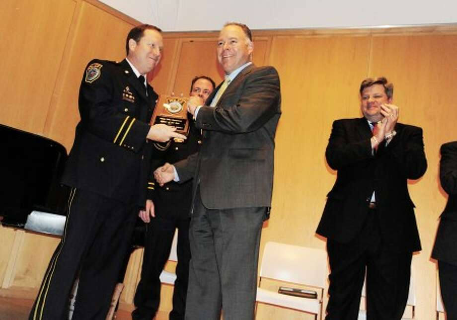 Detective Christopher Isidrois recieves the Police Officer of the Year award and is greeted by Deputy Chief Robert Crosbay Monday night at the Wilton Police Department''s Annual Awards Ceremony at the Wilton Library. photo/matthew vinci