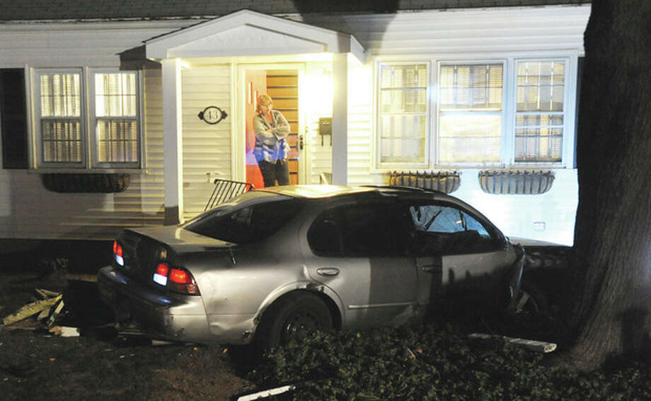 Hour photo/John Nash - A car allegedly used in the armed robbery of a jewelry on Westport Ave., was involved in a car crash on George Ave. in Norwalk on Friday night. One suspect was apprehended with the help of a police dog while two other suspects remained uncaptured early Friday evening.
