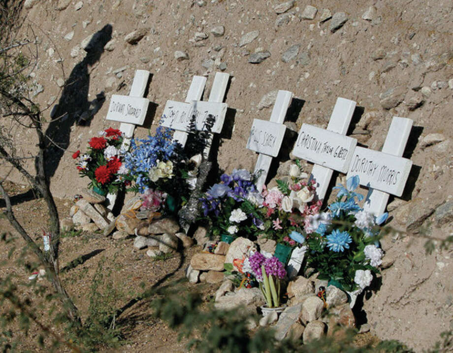 Six memorial markers with the names of those who were killed in a shooting spree are displayed Sunday in Tucson, Ariz. / AP