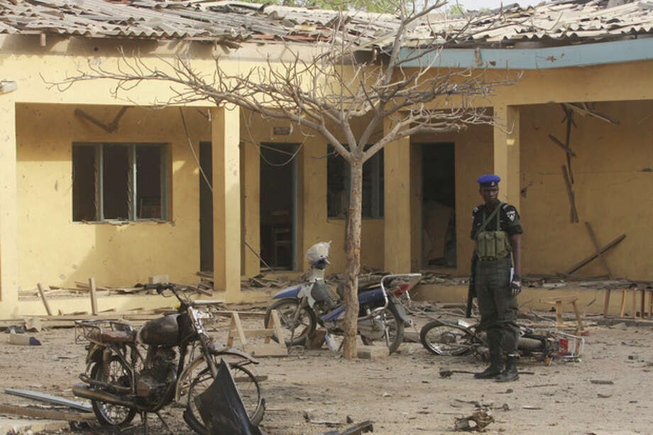 A policeman stands guard near the site of the police headquarters bombed by a suicide bomber in Kano, Nigeria, Sunday, Jan. 22, 2012. More than 150 people were killed in a series of coordinated attacks by a radical Islamist sect in north Nigeria's largest city, according to an internal Red Cross document seen Sunday by an Associated Press reporter. (AP Photo/Sunday Alamba) / AP