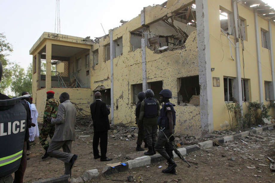 Police and civilians visit the site of the police headquarters bombed by a suicide bomber in Kano, Nigeria, Sunday, Jan. 22, 2012. More than 150 people were killed in a series of coordinated attacks by a radical Islamist sect in north Nigeria's largest city, according to an internal Red Cross document seen Sunday by an Associated Press reporter. (AP Photo/Sunday Alamba) / AP