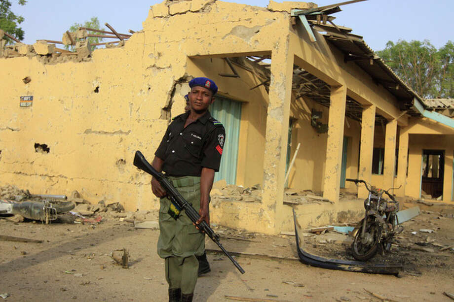A police officer stands guard at the site of a suicide bombing at the police headquarters in Kano, Nigeria. Sunday, Jan. 22, 2012. More than 150 people were killed in a series of coordinated attacks by a radical Islamist sect in north Nigeria's largest city, according to an internal Red Cross document seen Sunday by an Associated Press reporter.(AP Photo/Sunday Alamba) / AP