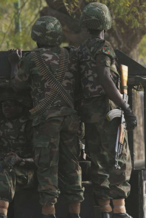 Soldiers ride on a back of a truck prior to Nigerian President Goodluck Jonathan's visit to the site of the suicide bombing at the police headquarters Kano, Nigeria, Sunday, Jan. 22, 2012. More than 150 people were killed in a series of coordinated attacks by a radical Islamist sect in north Nigeria's largest city, according to an internal Red Cross document seen Sunday by an Associated Press reporter. (AP Photo/Sunday Alamba)