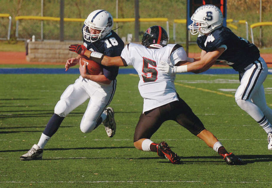 Hour photo/Erik Trautmann Staples quarterback Jack Massie, left, looks to race past a Fairfield Warde defender as teammate James Frusciante blocks during a regular season game this fall. / (C)2011, The Hour Newspapers, all rights reserved