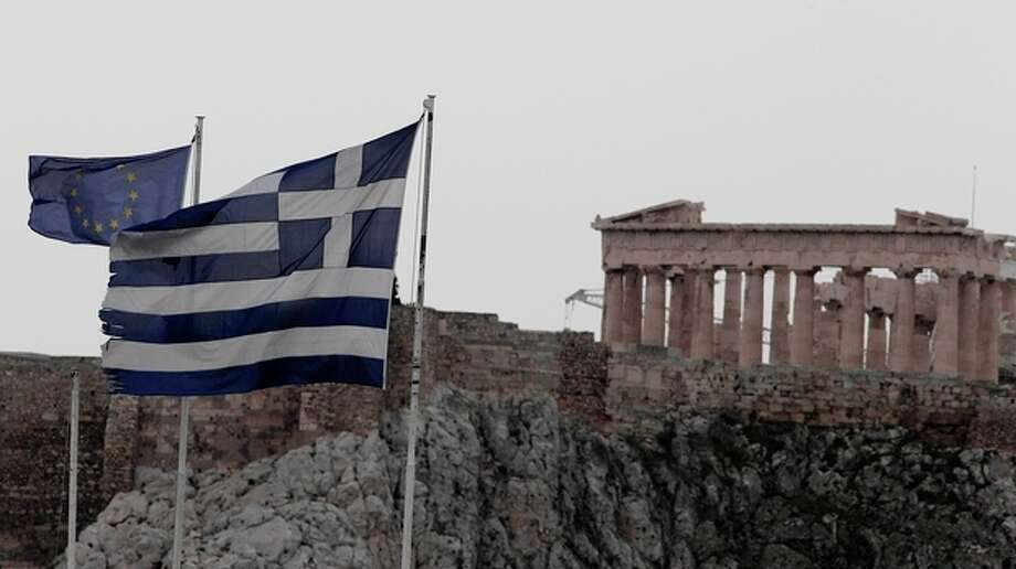 The flags of Greece, right, and European Union flutter from the roof of the Finance Minister at Athens' main Syntagma square, as in the background is seen the ancient Parthenon temple during in Athens on Thursday Feb, 9, 2012. Greek Prime Minister Lucas Papademos and his coalition partners have struck a deal on new cuts demanded by creditors to secure a vital euro130 billion bailout. (AP Photo.Dimitri Messinis) / AP