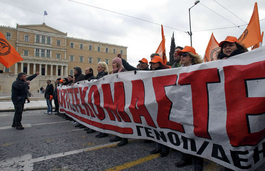 Employees of electricity company Public Power Corporation, PPC, shout slogans as they hold a banner reading: ''We resist'' during a protest against Greek government's plans to privatize part of the power distribution service, outside the Greek Parliament in Athens, on Thursday, Feb. 9, 2012. Greece's crucial euro 130 billion ($173 billion) bailout was in limbo Thursday, after political leaders failed to accept the entire batch of new austerity measures that are demanded by creditors but have fueled outrage in the recession-hit country. (AP Photo/Thanassis Stavrakis) / AP
