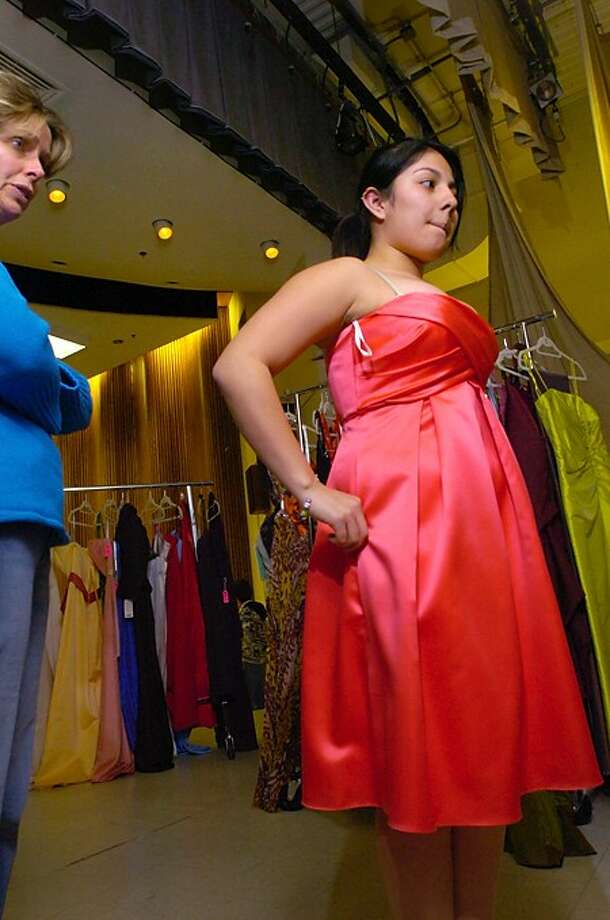 Westhill High School PTO volunteer Eileen Westfahl helps sophmore Diana Palma find a dress for the senior prom during the school''s annual Prom Gown Sale Friday. Hour photo / Erik Trautmann