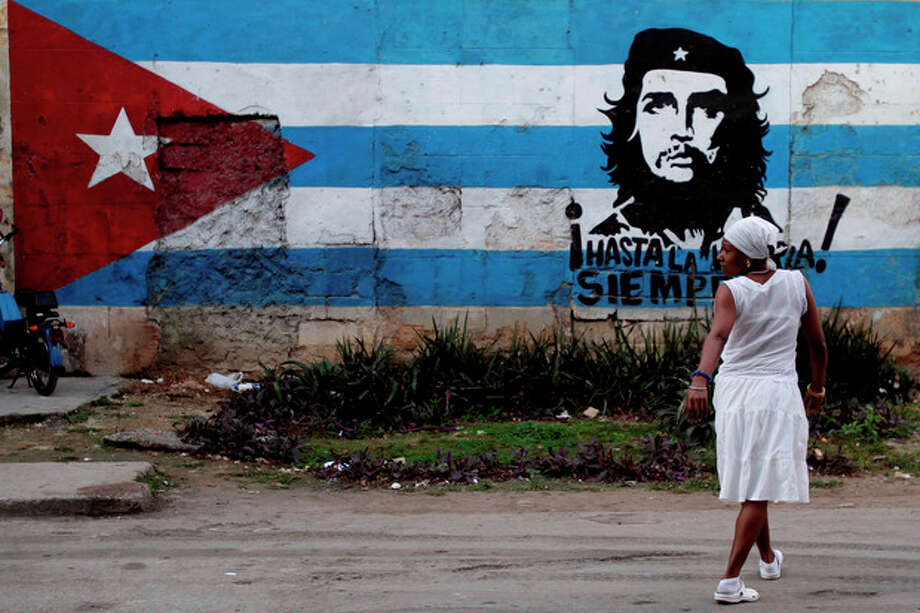 "A santera looks back while crossing the street where a wall is covered with a mural of the Cuban flag and an image of Cuba's revolutionary hero Ernesto ""Che"" Guevara in Havana, Cuba, Friday Jan. 27, 2012. After economic reforms by President Raul Castro were endorsed by the communist congress in mid-2011, the Communist Party of Cuba (PCC) is preparing to hold a party conference this weekend. (AP Photo/Franklin Reyes) / AP"