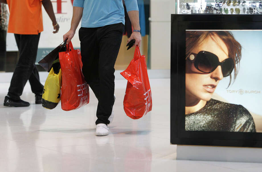 In this Nov. 9, 2011 file photo, a shopper carries purchases while shopping at Dolphin Mall, in Miami. Consumer spending was flat in December while incomes rose by the largest amount in nine months. But even with the December income surge, incomes for the whole year were up just half the amount of 2010, underscoring the challenge facing the economy. (AP Photo/Lynne Sladky, File) / AP2011