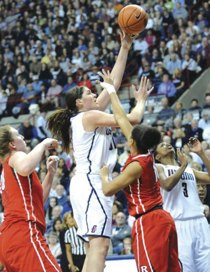 AP photo UConn's Stefanie Dolson goes up for a shot over Christa Evans, left, and Briyona Canty of Rutgers in the first half of Saturday night's game. Dolson had 16 points to lead the Huskies to a 66-34 victory.