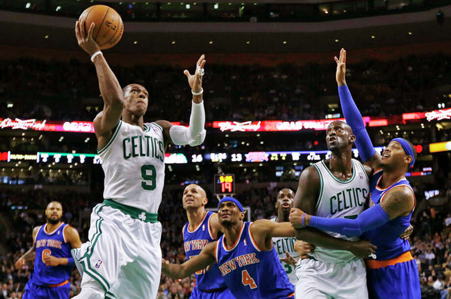 Boston Celtics guard Rajon Rondo (9) drives to the basket as Kevin Garnett blocks out New York Knicks forward Carmelo Anthony, right, during the first quarter of an NBA basketball game in Boston, Thursday, Jan. 24, 2013. (AP Photo/Charles Krupa) / AP