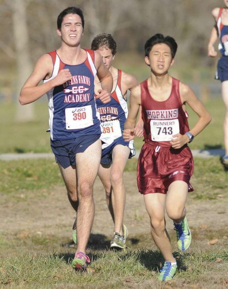 Hour photo/John Nash Peter Maturo, left, and Andrew McCarthy of Greens Farms Academy keep pace with a Hopkins runner during Monday's FAA cross country championship meet in Westport. Maturo finished fifth and McCarthy sixth in the meet. The defending champion GFA boys finished third.
