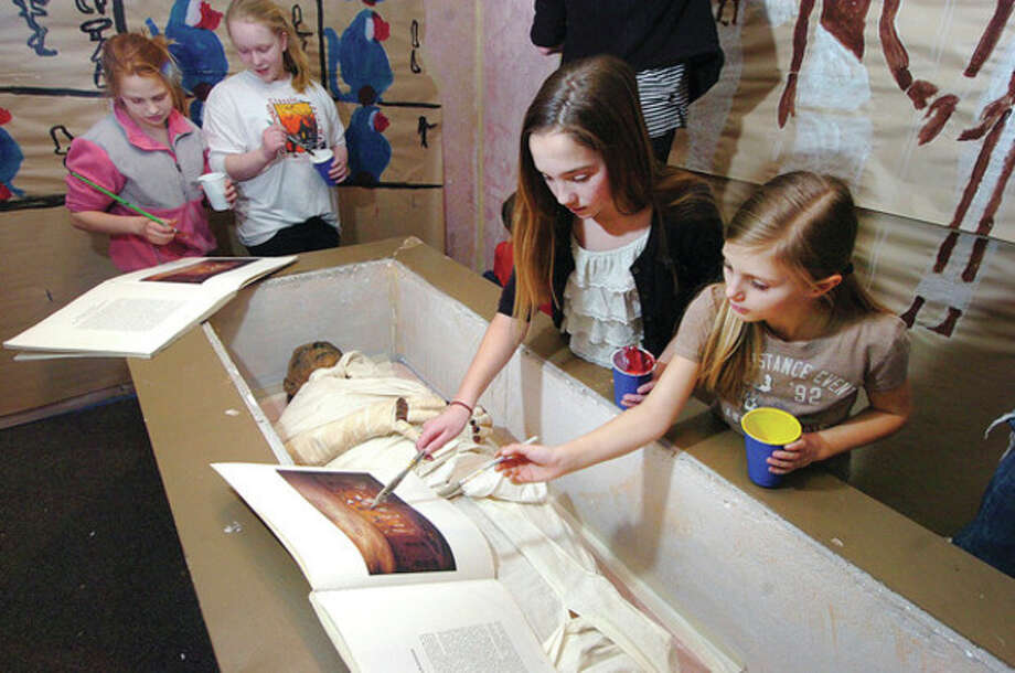 Photo/ Alex von Kleydorff. Sixth graders Emily Logan and Lilly Benson refer to a book to paint the 'opening of the mouth' mural in the burial chamber of King Tut at Middlebrook School. / © 2012 The Hour Newspapers