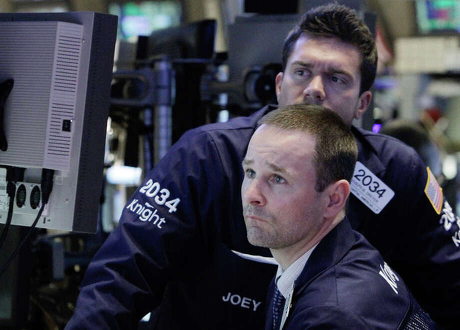 FILE - In this Jan. 10, 2012 photo, a pair of specialists study a screen as they work on the floor of the New York Stock Exchange. Strong bond auctions in Italy and Spain dramatically drove down their borrowing costs and lifted stocks Thursday, Jan. 12, 2012, providing a reprieve from Europe's relentless debt crisis. (AP Photo/Richard Drew, File) / AP