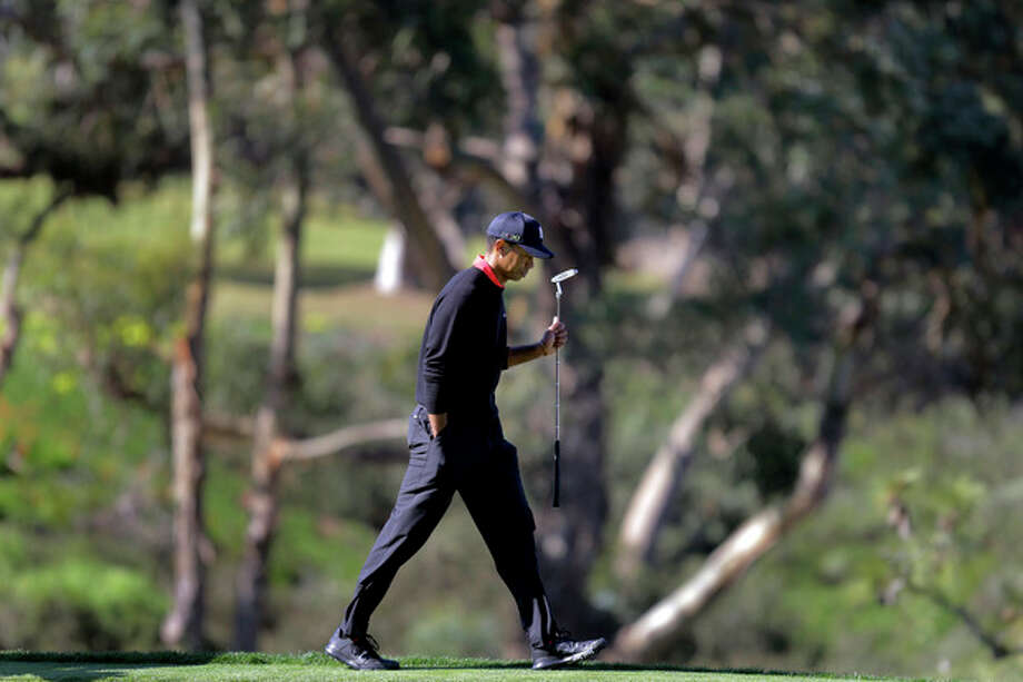 Tiger Woods takes a look at the green before putting on the 13th hole during the fourth round of the Farmers Insurance Open golf tournament at the Torrey Pines Golf Course, Monday, Jan. 28, 2013, in San Diego. (AP Photo/Lenny Ignelzi) / AP