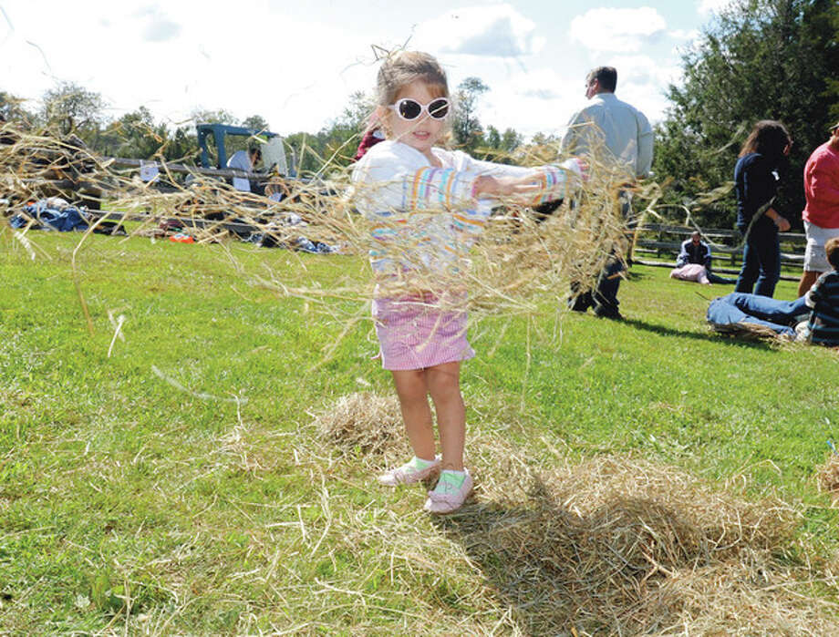 Rebecca Keena, 3, plays in the hay at the 11th annual Ambler Farm Day in Wilton in 2011. Photo by Matthew Vinci.