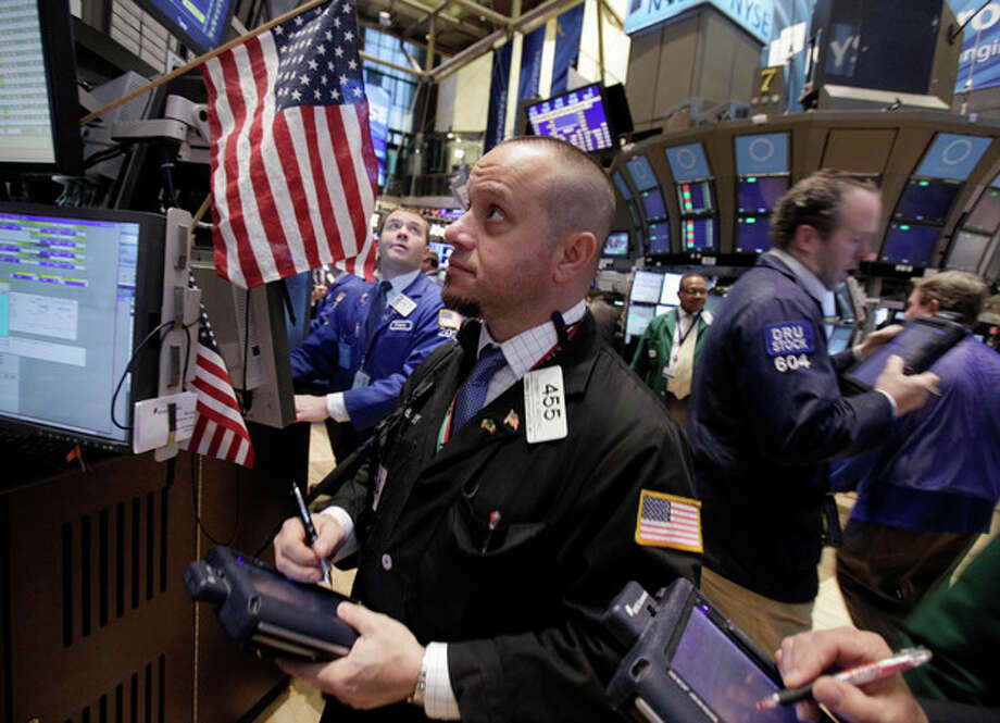 Trader Robert Arciero, center, works on the floor of the New York Stock Exchange Tuesday, Jan. 10, 2012. Stocks are shooting higher after the market opened on comforting news from Europe and an optimistic outlook from corporate bellwether Alcoa. (AP Photo/Richard Drew) / AP