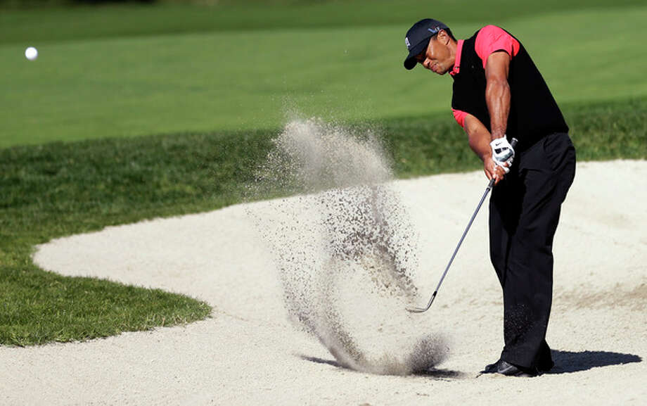 Tiger Woods hits out of a bunker on the 10th hole during the fourth round of the Farmers Insurance Open golf tournament at the Torrey Pines Golf Course, Monday, Jan. 28, 2013, in San Diego. (AP Photo/Gregory Bull) / AP