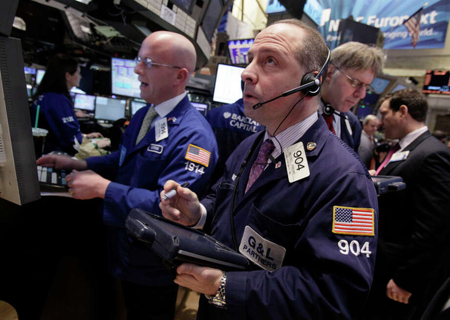 Trader Michael Urkonis, center, works on the floor of the New York Stock Exchange Tuesday, Jan. 10, 2012. Stocks are shooting higher after the market opened on comforting news from Europe and an optimistic outlook from corporate bellwether Alcoa. (AP Photo/Richard Drew) / AP