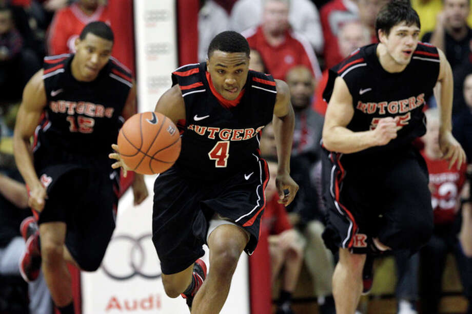 Rutgers' Myles Mack (4) leads teammates Gilvydas Biruta, of Lithuania, right, and Derrick Randall as he dribbles the ball during the first half of an NCAA college basketball game against Connecticut in Piscataway, N.J., Saturday, Jan. 7, 2012. (AP Photo/Mel Evans) / AP