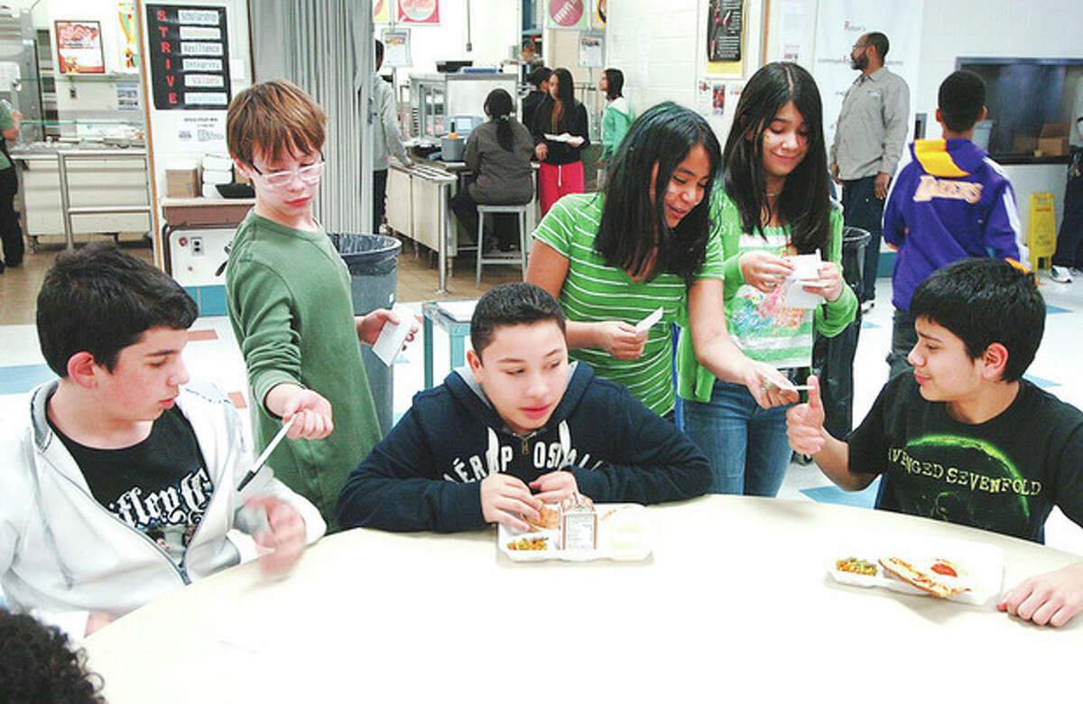 """Hour photo / Alex von Kleydorff Roton Middle School seventh-graders Johnathan Miller, Jasmine Portugal and Jocelyn Moran pass out pens and paper to students to write messages of inspiration to students from Sandy Hook Elementary School during lunch period on """"Love for Sandy Hook Day"""" Monday."""